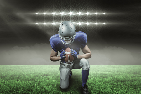 American football player kneeling against spotlights with copy space 3d Stock Photo