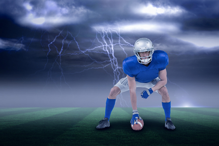 Alert American football player in attack stance against stormy dark sky with lightning bolts with copy space 3d