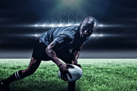 kick around: Determined sportsman looking away while playing rugby against spotlights and copy space 3d Stock Photo