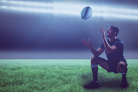 kick around: Full length of rugby player catching the ball against spotlight with copy space 3d
