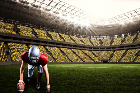 American football player taking position while holding ball against large football stadium with fans in yellow with copy space 3d