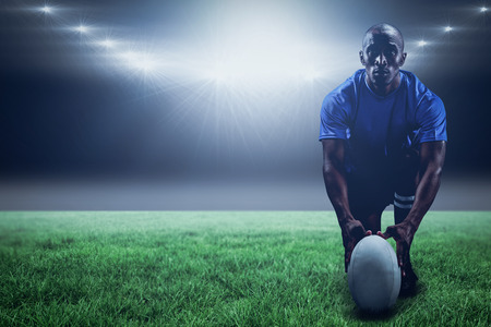 kick around: Portrait of rugby player holding ball while kneeling against spotlight and copy space 3d