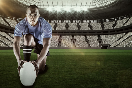 kick around: Portrait of rugby player kneeling and holding ball against rugby stadium with copy space 3d Stock Photo