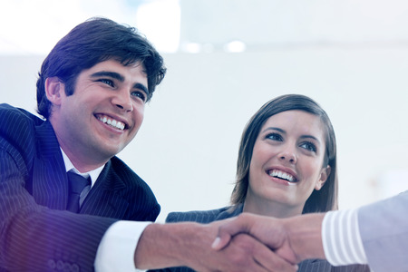 stipulation: Smiling businessman and his colleague closing a deal with a partner in a meeting Stock Photo