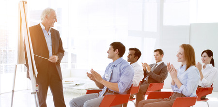 Business people applauding at the end of a conference in the office Stock Photo