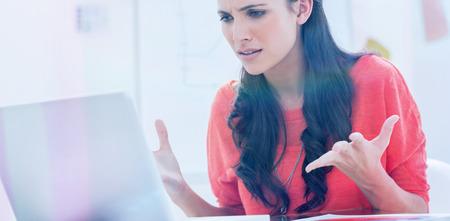 イライラのデザイナーが彼女のオフィスで彼女のラップトップの前で身振りで示す