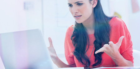 out of business: Annoyed designer gesturing in front of her laptop in her office Stock Photo