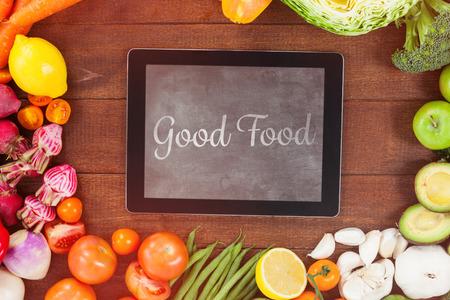 comida rica: buena comida contra la tableta digital rodeada de verduras frescas Foto de archivo