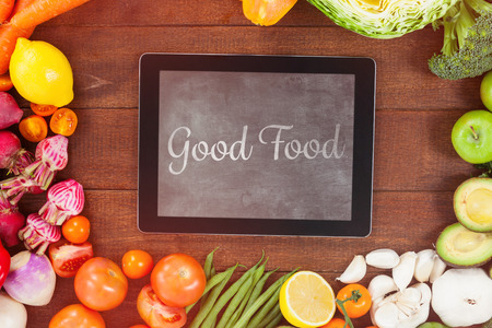 good food: good food against digital tablet surrounded with fresh vegetables
