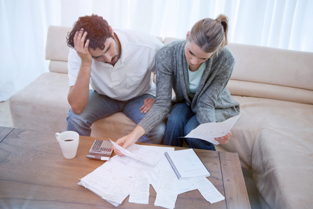 Depressed couple doing their accounting in their living room