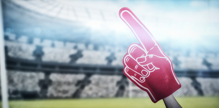 American football player holding supporter foam hand against digital image of rugby stadium with copy space 3d