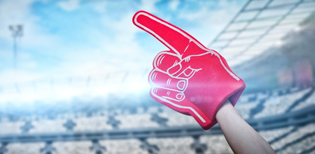 American football player holding supporter foam hand against rugby stadium with copy space 3d