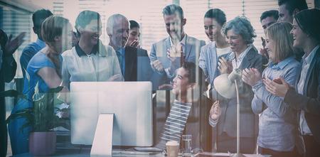 Gente de negocios aplaudiendo la presentación de su colega en la oficina vista a través del vidrio