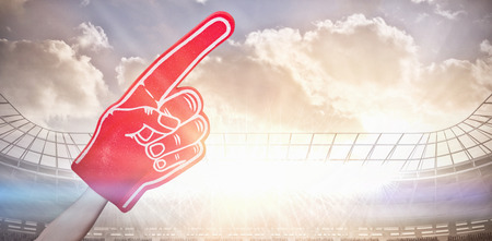 American football player holding supporter foam hand against large football stadium under cloudy blue sky with copy space 3d Stock Photo