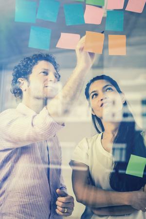 Geschäftsmann und Geschäftsfrau diskutieren über Haftnotizen auf Glaswand in Büro
