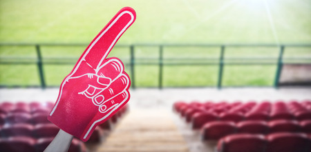 American football player holding supporter foam hand against red bleachers looking down on football pitch with copy space 3d