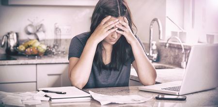 Stressed woman looking down at bills in kitchen
