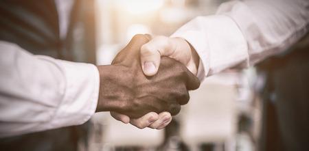 Bebouwd beeld van zakenman het schudden hand met collega in bureau Stockfoto - 69609261