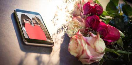 geeky: Mobile phone on table  against composite image of geeky hipsters kissing behind heart card Stock Photo