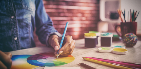 Grafisch ontwerper die op kleurengrafiek trekt op het werk Stockfoto