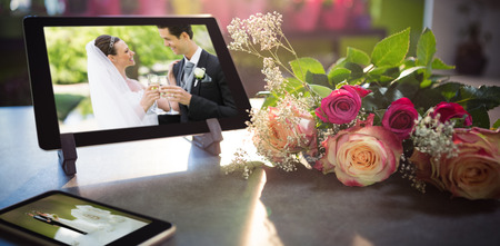 Mobile phone and tablet on table against wedding cake figurine
