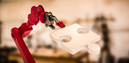 mano robotica: Digital image of red robotic hand holding puzzle piece against equipment on desk 3d