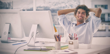 notebook design: Portrait of a relaxed casual young business man with computer in a bright office