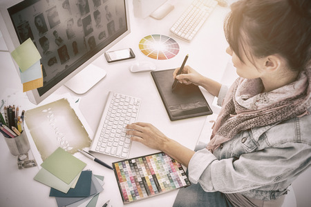 High angle view of an artist drawing something on graphic tablet at the office Foto de archivo