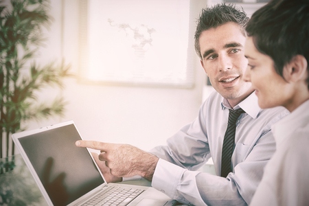 Manager pointing at something to his secretary on a laptop in an office Stock Photo