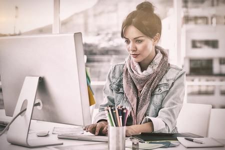 robo: Concentrada que usa el ordenador mujer joven casual en una oficina brillante Foto de archivo
