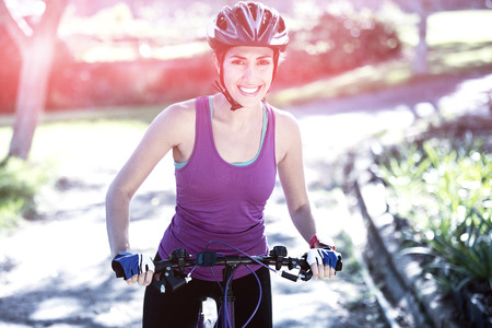 Portrait of female cyclist cycling in countryside on sunny day
