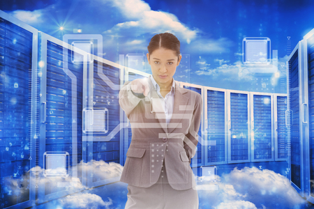 Portrait of a serious businesswoman pointing at the viewer against server room in blue Stock Photo