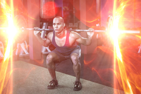 receding: Full length of young man weightlifting in fitness studio