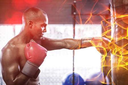 punched out: Side view of male boxer punching bag in fitness studio