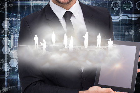 well dressed: Smiling businessman showing his tablet pc against hologram background