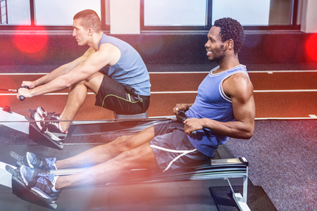 half ball: Muscular men using rowing machine at gym Stock Photo