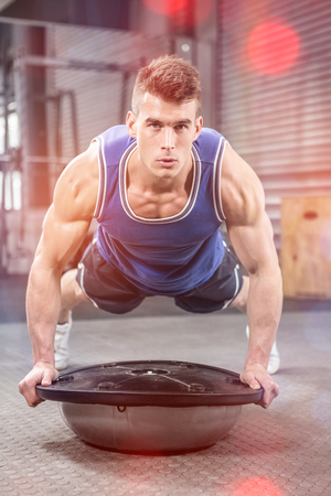 plank position: Muscular man doing push up on bosu ball at crossfit gym