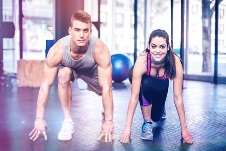 Athletic couple stretching at gym