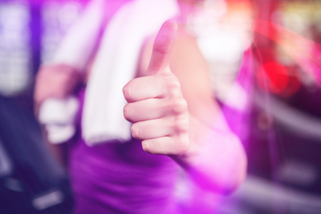 Woman showing her thumbs up at gym