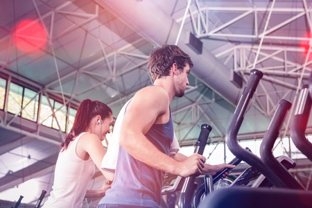 Beautiful woman and man exercising on elliptical machine at gym