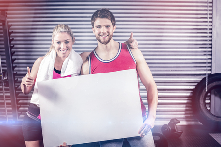 Fit couple holding blank paper at crossfit gym