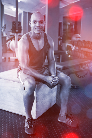 receding: Portrait of male athlete sitting on wooden box in fitness studio