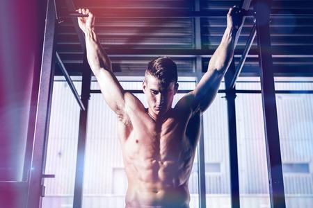 Shirtless man doing pull up at gym
