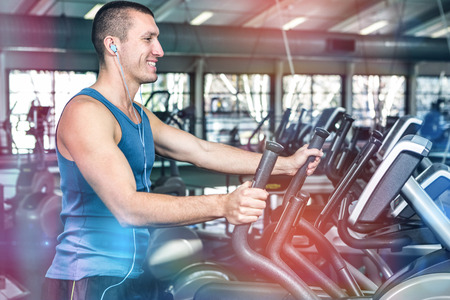 Smiling muscular man using elliptical machine at gym Stock Photo