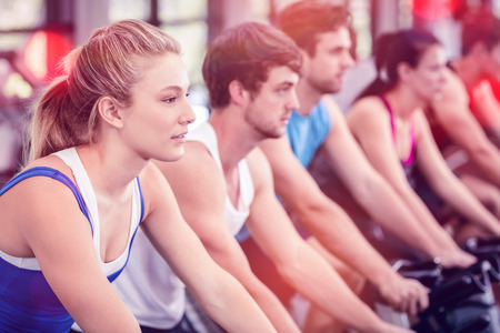 Fit group of people using exercise bike together in gym Stock Photo