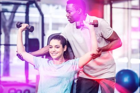levantando pesas: La mujer Athletic de levantamiento de pesas ayudado por el entrenador en el gimnasio Foto de archivo
