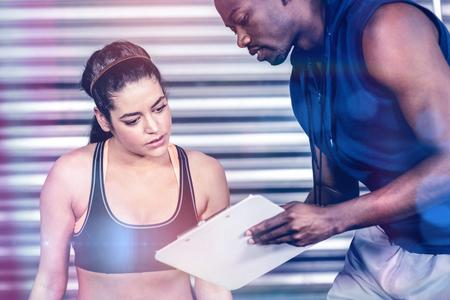 koncentrovaný: Athletický trenér vysvětluje plán cvičení ženě v crossfit tělocvičně