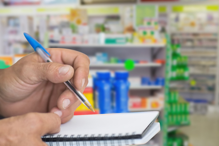 pharmaceutical company: Close up of man writing in notepad against close up of shelves of drugs
