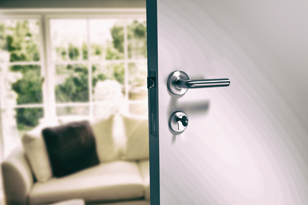 Closeup of metal doorknob and lock with key against sitting room Reklamní fotografie