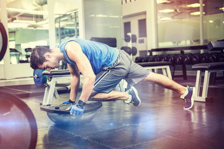 plank position: Muscular man exercising with bosu ball in gym Stock Photo